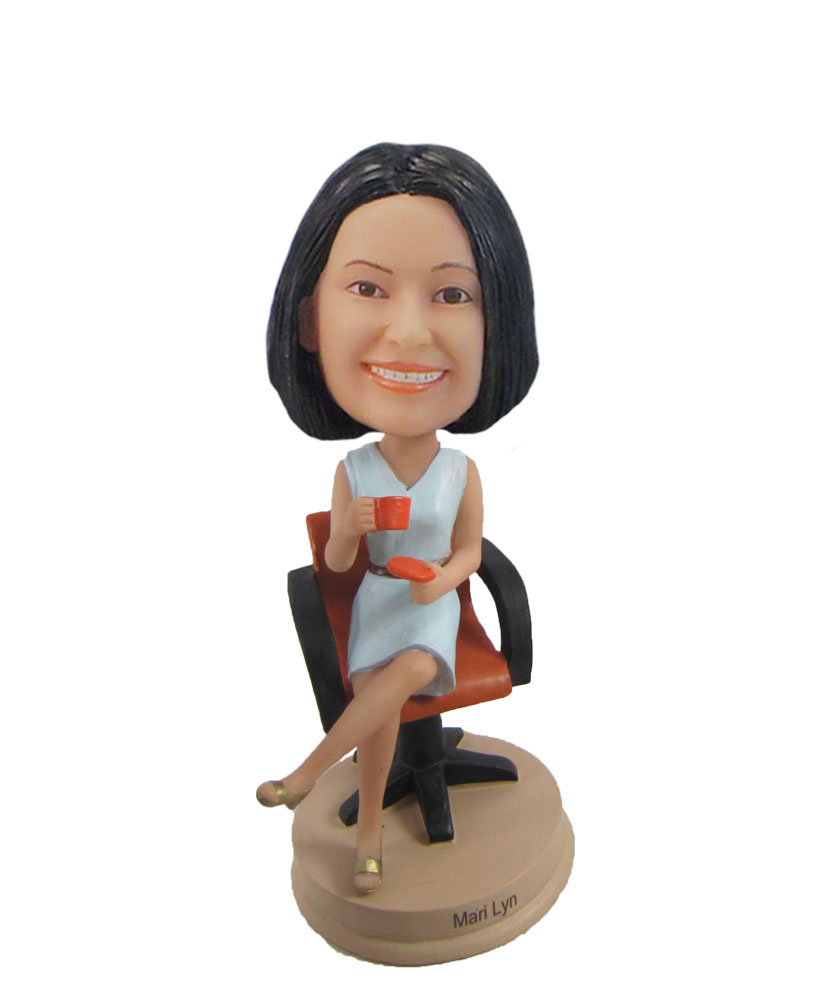 Female bobblehead holding cup on chair F1055